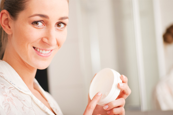 Woman applying facial lotion