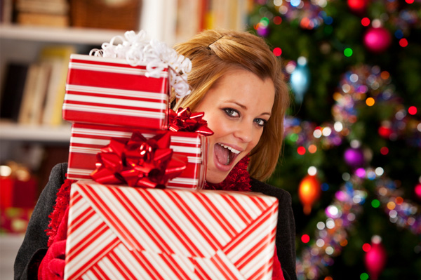Woman with pile of Christmas gifts