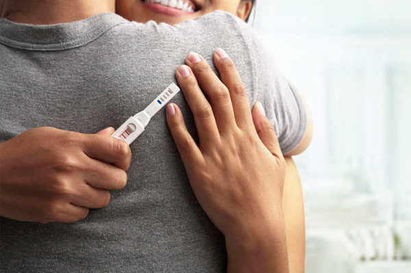 Couple embracing with positive pregnancy test
