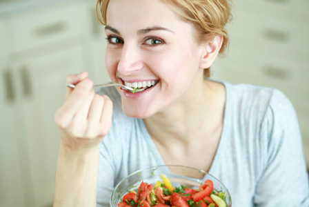 Happy woman eating DASH diet meal