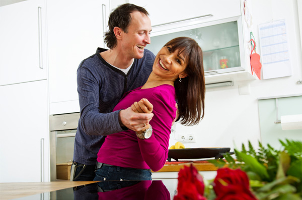 Husband and wife dancing in kitchen