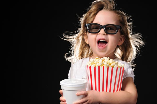 Little girl at movie theater in 3D glasses