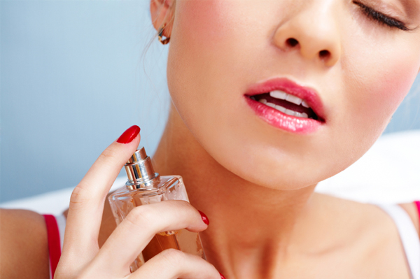 Sexy woman applying perfume