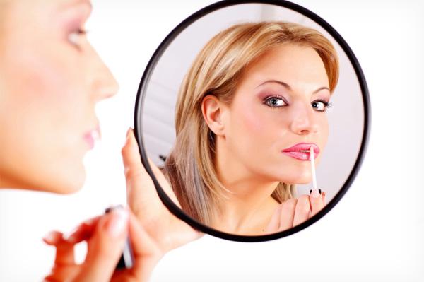 Woman applying globs of makeup