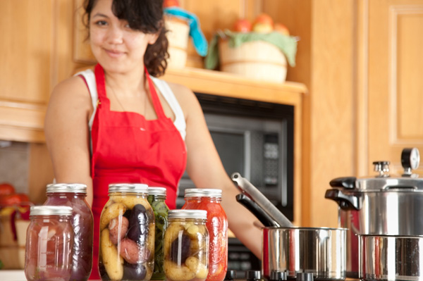 Woman canning vegetables at home