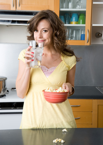 Woman drinking water and eating air popped popcorn