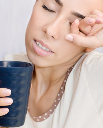 Woman drinking coffee and rubbing eyes