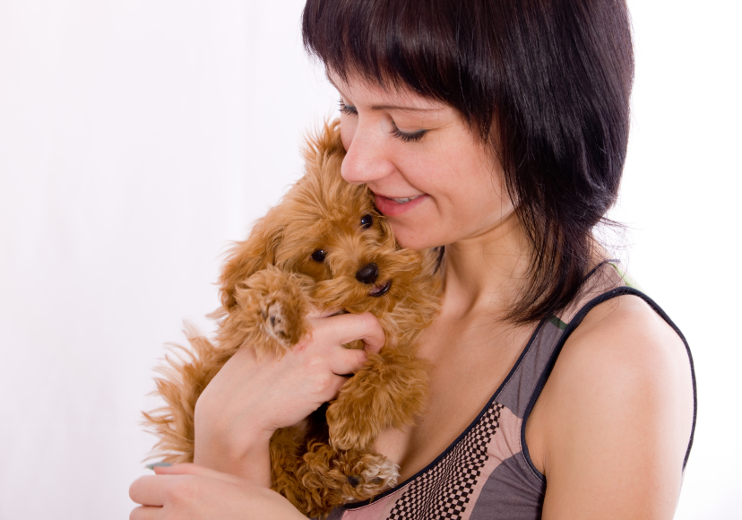 Young woman cudding with small dog
