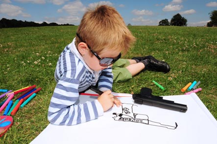 Boy drawing picture of gun