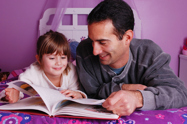 Single dad reading a book with daughter