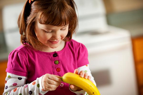 Little girl peeling banana for snack
