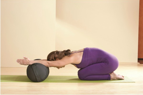 Woman using an inflatable yoga bolster