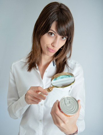 Skeptical woman reading label on can