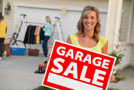 Woman holding garage sale sign