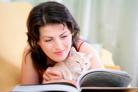 Woman reading with cat