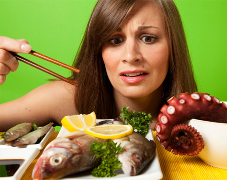 Woman eating sushi that is alive