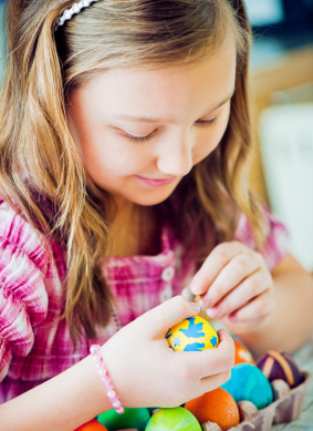 Girl coloring Easter Eggs