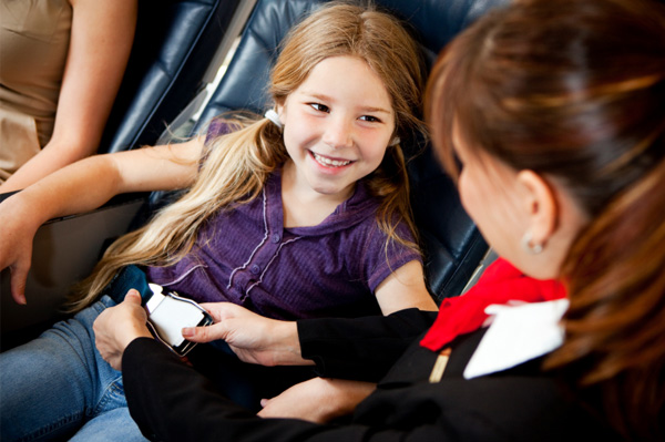 Little girl being buckled into airplane seat