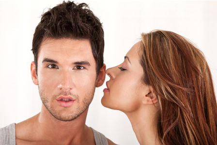 Sexy woman whispering into her boyfriend's ear