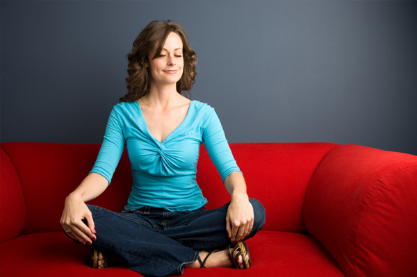 Woman on red couch doing yoga