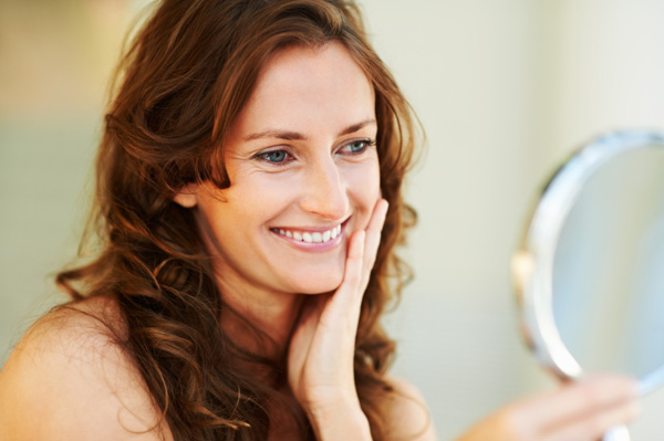 Woman with white teeth looking in mirror