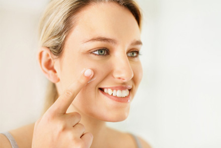 Woman applying tinted moisturizer