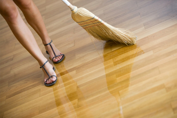 Woman sweeping wood floor