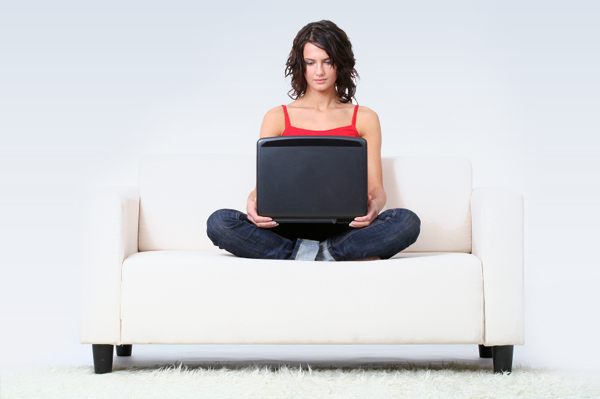 woman sitting on white couch with laptop