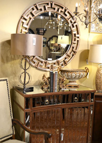 A mirrored table, decorative mirror, and metalic accents makes this vignette shine.