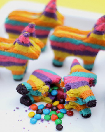 3 pinata cookies made out of multicolored cookies filled with mini m&m's.