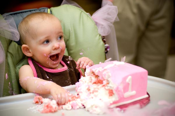 baby girl eating first birthday cake