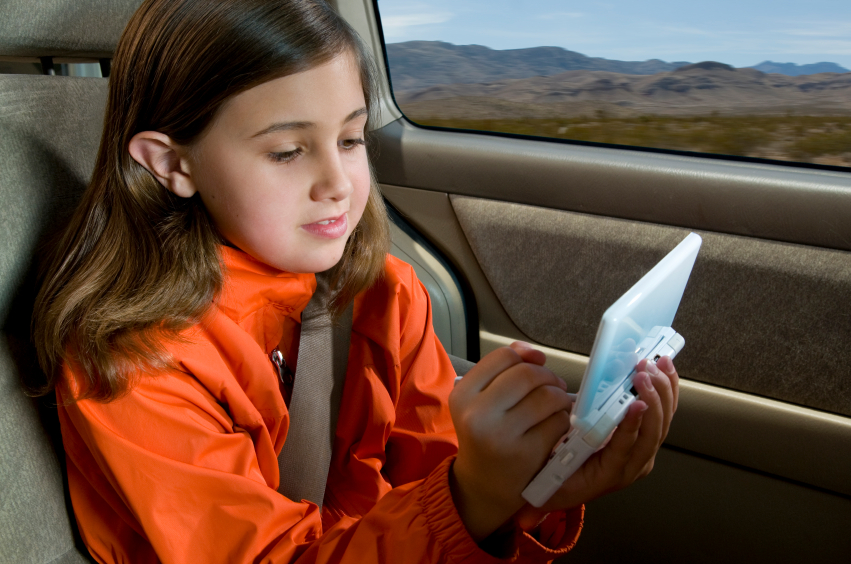 girl on roadtrip playing gameboy