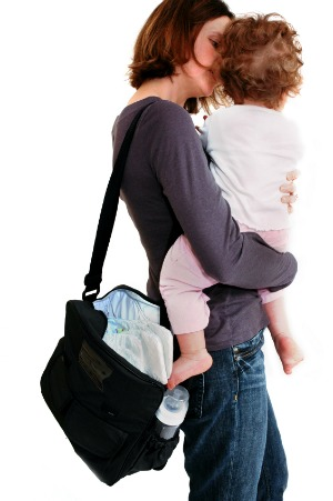 mom holding toddler with diaper bag on shoulder