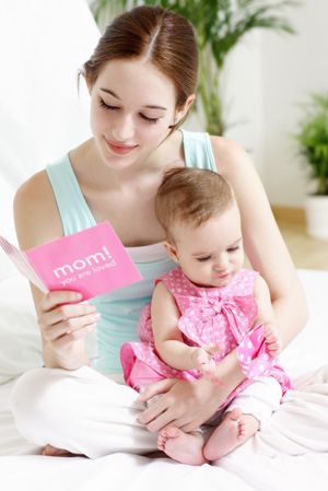 new mom holding baby and mothers day card