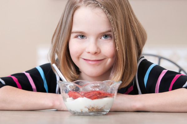 Tween girl eating yogurt