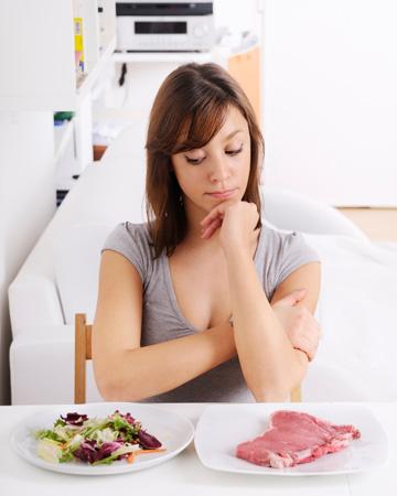 Woman choosing between meat and salad