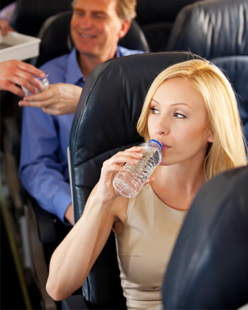 Woman drinking water on plane