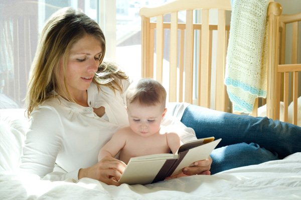 mom reading to baby in bed