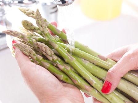 Woman washing asparagus