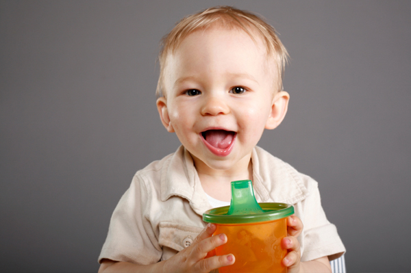 Baby boy and sippy cup with juice