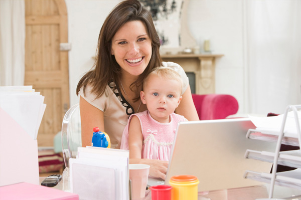 mom working on laptop with toddler
