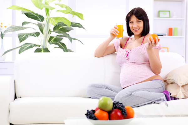 Pregnant woman eating an orange