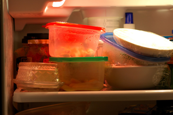 improperly stored leftovers in crowded refrigerator