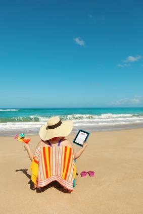 woman relaxing on beach with an ereader