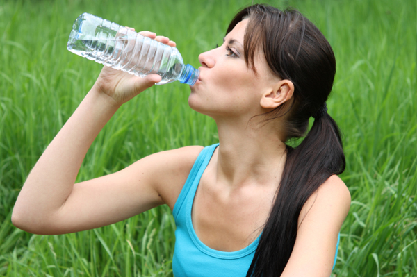 woman drinking water during summer