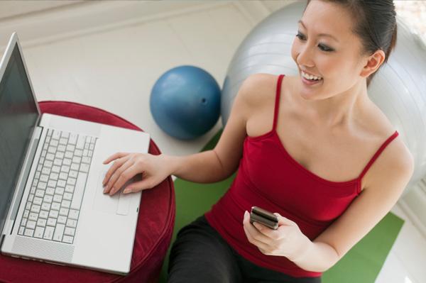 Woman exercising near computer