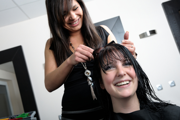 Woman getting haircut in salon
