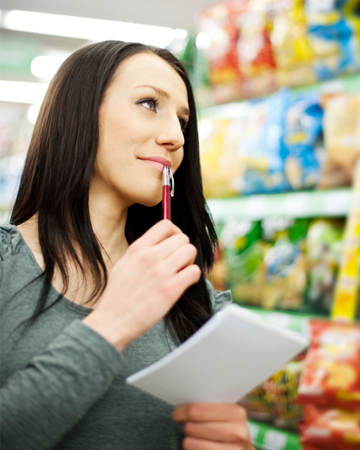 Woman grocery shopping with list