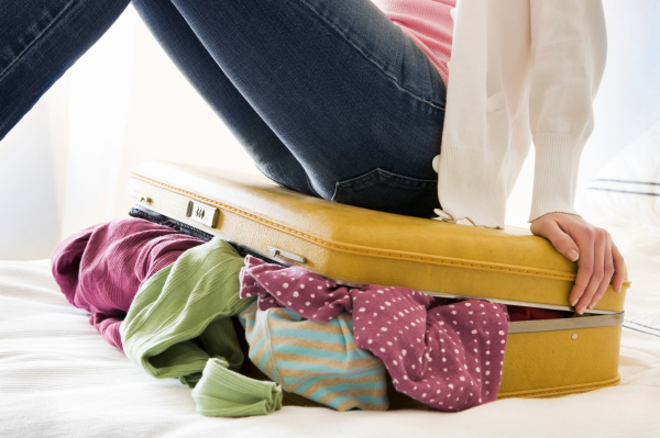 woman trying to close packed suitcase