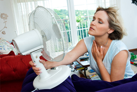 Woman with small fan keeping cool